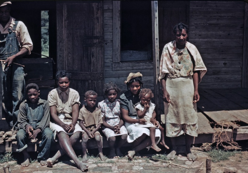 Marion Post Wolcott - Bayou Bourbeau plantation, a FSA cooperative, Natchitoches, Louisiana. A Negro family seated on the porch of a house, 1940